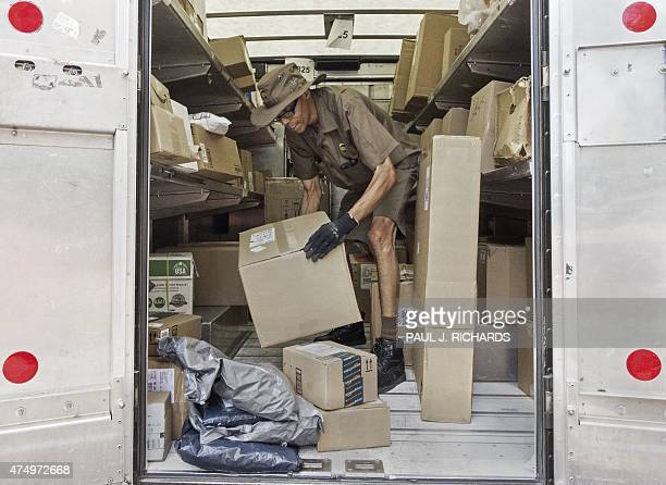A United Parcel Serice driver sorts packages for delivery in the back of his truck May 28 in Washington DC AFP PHOTO/PAUL J RICHARDS