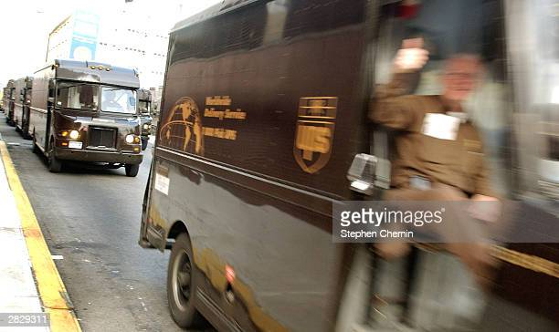 United Parcel Service delivery man gives a thumbs up as he leads a line of UPS trucks out of the 43rd Street UPS depot December 23 2003 in New York...