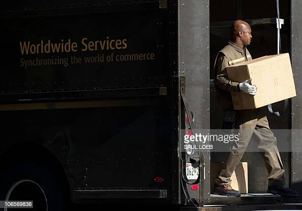 A United Parcel Service delivery man unloads boxes from his truck outside a business in Washington DC November 5 2010 AFP PHOTO / Saul LOEB