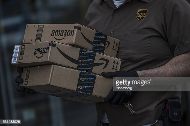A United Parcel Service Inc delivery driver carrries Amazoncom Inc packages near the Fulton Street Mall in the Brooklyn borough of New York US on...