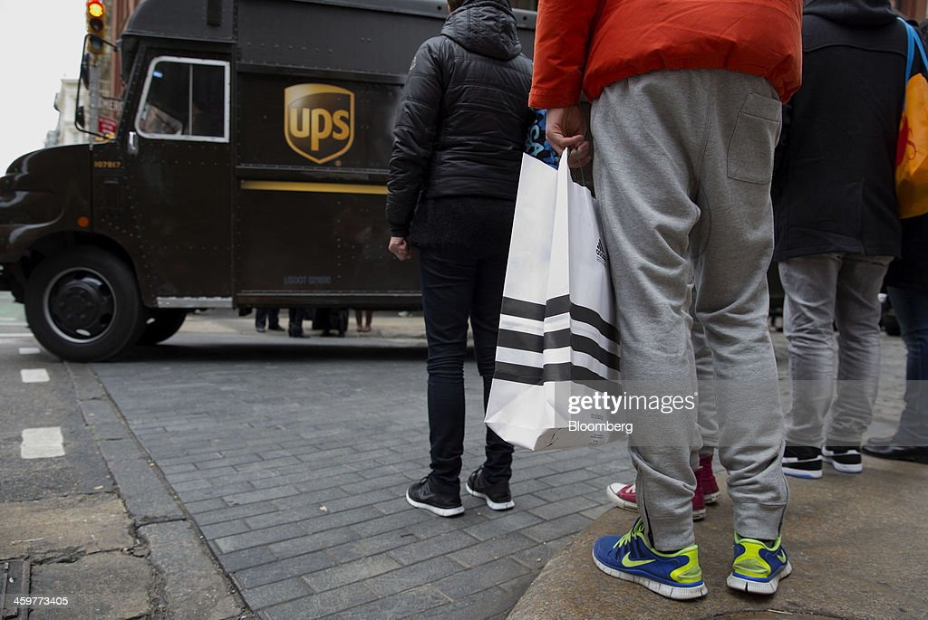 A United Parcel Service Inc. (UPS) truck drives past shoppers in the Soho neighborhood of New York, U.S., on Monday, Dec. 30, 2013. The failure of UPS and FedEx Corp. to deliver packages in time for Christmas has exposed the perils of retailers promising to get last-minute gifts to customers. Photographer: Jin Lee/Bloomberg via Getty Images