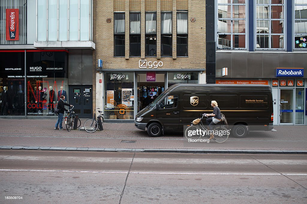 A United Parcel Service Inc. (UPS) truck sits parked as a cyclist passes a Ziggo NV store in Utrecht, Netherlands, on Friday, Oct. 4, 2013. Cable-TV provider Ziggo, which is 28.5 percent owned by Liberty Global Plc, is pushing into the Dutch mobile market with low-priced packages, following a playbook pioneered by French discount operator Iliad SA. Photographer: Jasper Juinen/Bloomberg via Getty Images