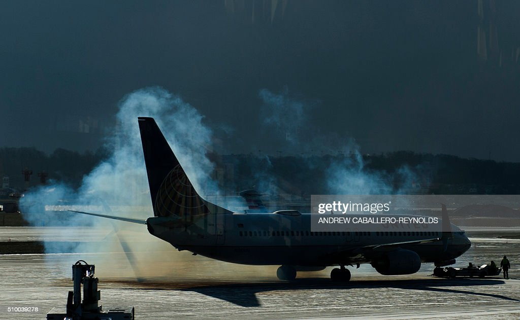 A United plane is covered in smoke as the engines start up at Ronald Regan National Airport in Washington, DC, on February 13, 2016. / AFP / ANDREW CABALLERO-REYNOLDS