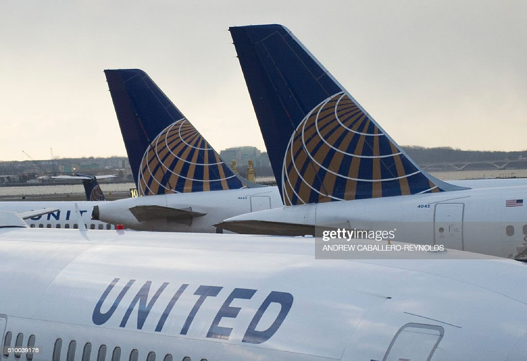 United planes are parked in the terminal at Ronald Regan National Airport in Washington, DC, on February 13, 2016. / AFP / ANDREW CABALLERO-REYNOLDS