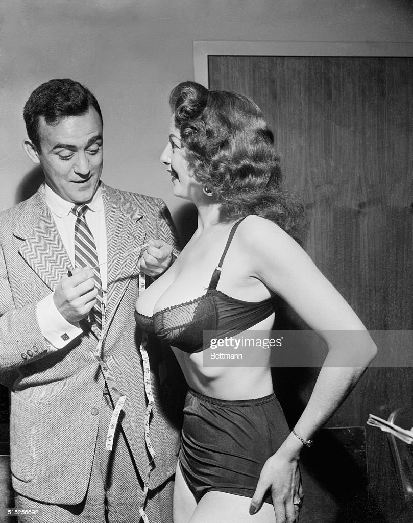 United Press Hollywood correspondent Vernon Scott muses over his tape measure after checking the dimensions of stripper Tempest Storm's curves Scott...