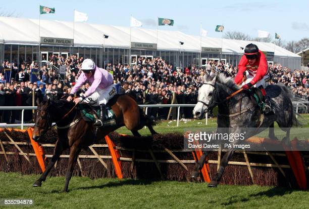 United ridden by Dominic Elsworth leads Fiveforthree ridden by Paul Townsend to go on and win the John Smith's Aintree Hurdle during the third day of...
