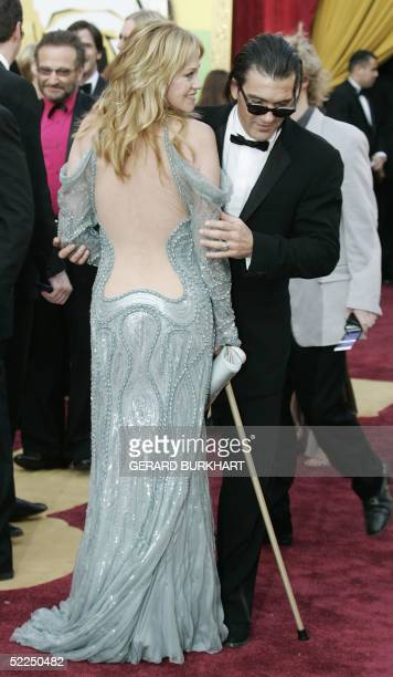 Actor Antonio Banderas shows off his wife's dress actress Melanie Griffith as they arrive for the 77th Academy Awards 27 February at the Kodak...