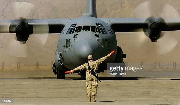 United States Air Force air marshal guides an Air Force C130 Hercules transport/cargo plane after it landed on the American military compound at...