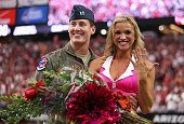 United States Air Force Captain Erick Straub stands with Arizona Cardinals cheerleader Claire Thornton after Straub proposed during the first half of...