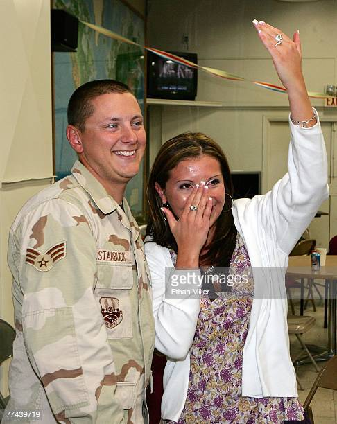 United States Air Force Senior Airman Andrew Starbuck from the 820th RED HORSE squadron smiles as Diana Gloria wipes away a tear as she shows off her...
