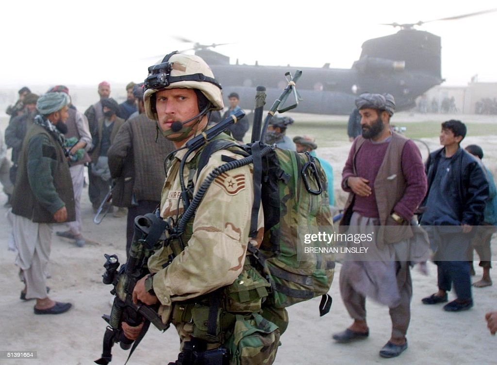 United States Air Force Special Operations soldier stands guard near a US Army Special Forces Chinook helicopter as Afghan civilians and militiamen...