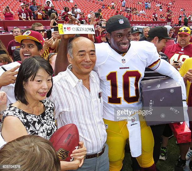 WASHINGTON United States American football star Robert Griffin III poses with Kenichiro Sasae Japanese ambassador to the United States and his wife...