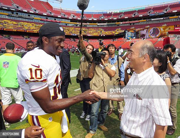 WASHINGTON United States American football star Robert Griffin III shakes hands with Kenichiro Sasae Japanese ambassador to the United States near...