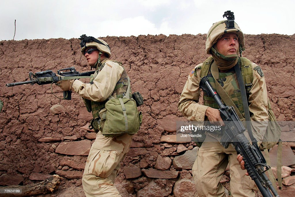 United States Army 10th Mountain soldiers keep an eye out for enemies as they take over dwellings March 8 2002 near the villages of Sherkhankheyl...