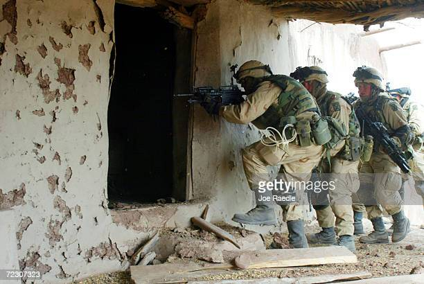 United States Army 10th Mountain soldiers prepare to enter a building as they search for al Qaeda and Taliban March 8 2002 near the villages of...