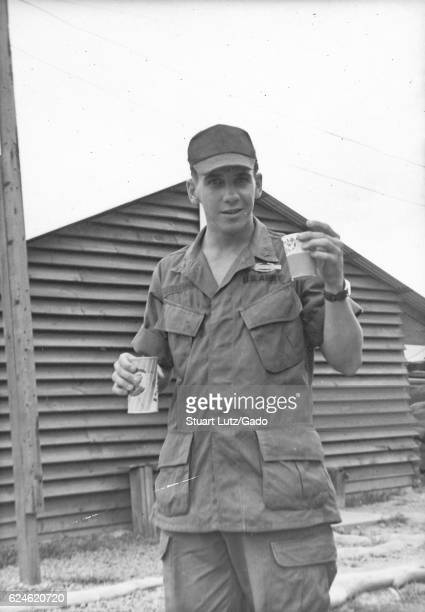 A United States Army serviceman in his uniform he is carrying a can of Pepsi in one hand and a paper cup in the other one of the wooden buildings on...