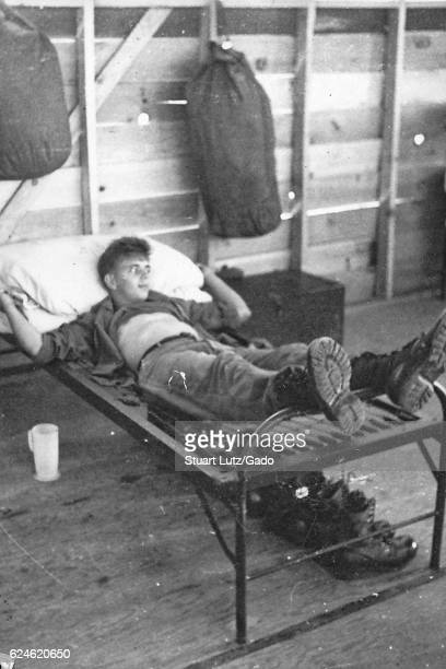 A United States Army serviceman laying on the springs of a bed without a mattress covering them duffel bags are hanging from the walls of the...