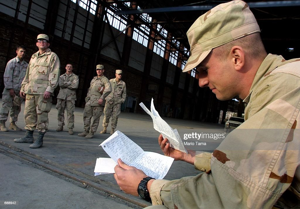 United States Army Sgt. Larry Casanova, of Haddon Township, NJ, reads a letter from his wife after eating Christmas dinner December 25, 2001 at Bagram Air Force Base in Kabul, Afghanistan. Many soldiers were able to call home on satellite phones to send holiday greetings to their families.