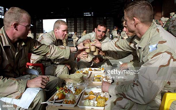 United States Army soldiers toast each other before eating Christmas dinner December 25 2001 at Bagram Air Force Base in Kabul Afghanistan Many...