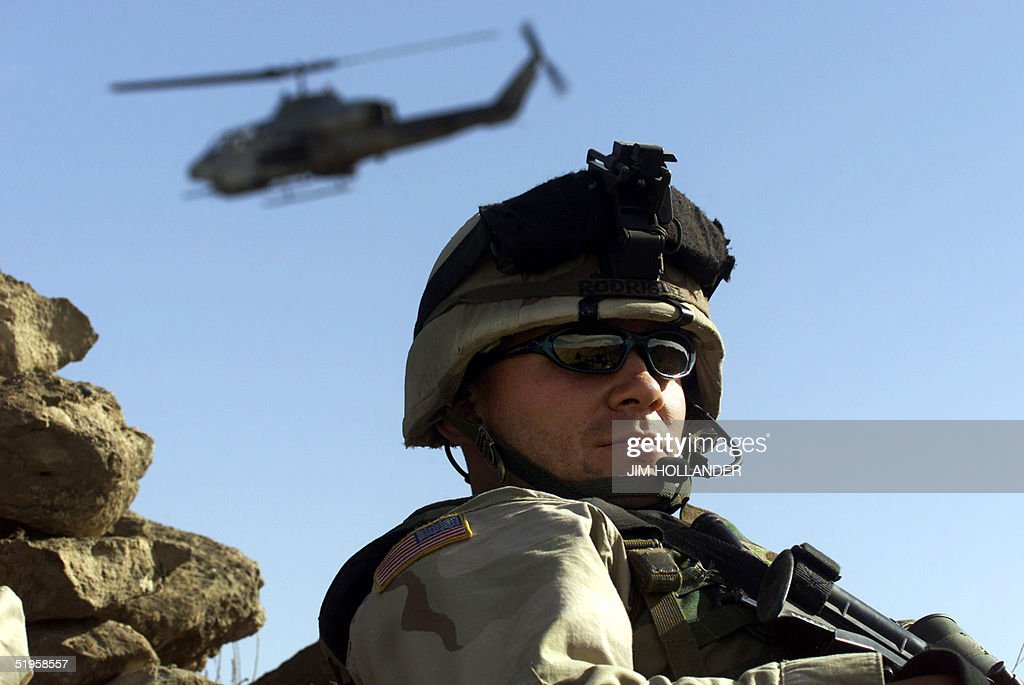 United States Army Staff Sergeant Del Rodriguez III of Fort Drum NY on a ridge in the Shahi Kot mountains 13 March 2002 as a US Army Cobra assault...