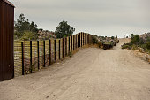 Jacumba, CA - NOVEMBER 27: United States international wall with Mexico and Border Patrol vehicle in the distance on November 27, 2017 in Jacumba, CA, USA.