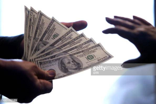 United States Dollar notes exchange hands at a local bank in Beijing 15 May 2006 China set its parity rate for the yuan at 80150 to the US dollar one...