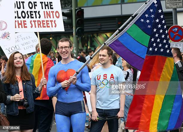 United States embassy employee Tim Standaert waves a rainbow American flag as he attends the Christopher Street Day gay parade in Berlin on June 27...