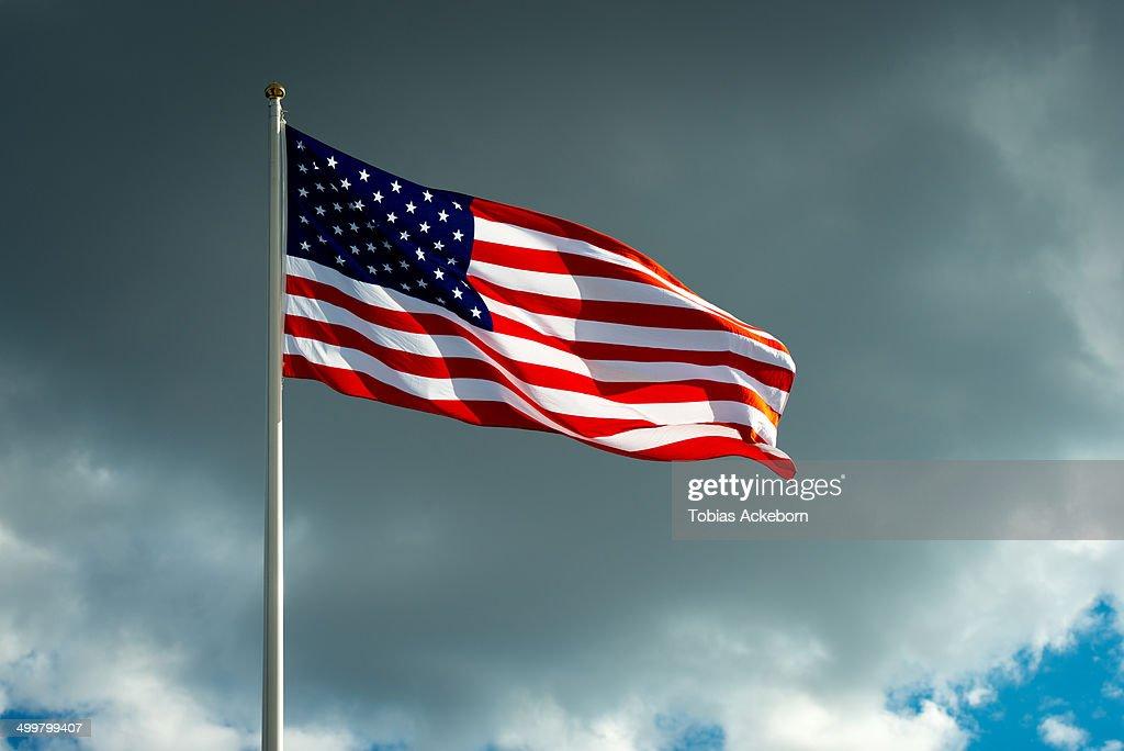 United States Flag against a dark clouds.