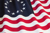 Historical United States flag with thirteen stars representing the original colonies
