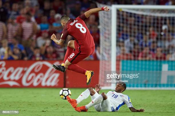 United States forward Clint Dempsey jumps over Panama midfielder Alberto Quintero to avoid a tackle during the World Cup Qualifying match between the...