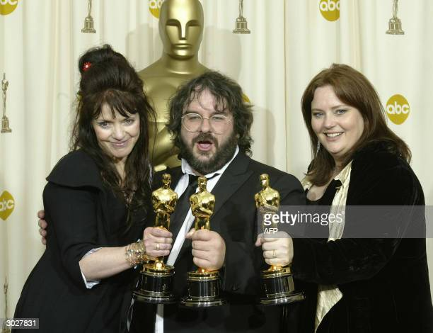 Fran Walsh kisses director Peter Jackson flanked by Philippa Boyens as they pose with the Oscar for Best Adapted Screenplay at the 76th Academy...