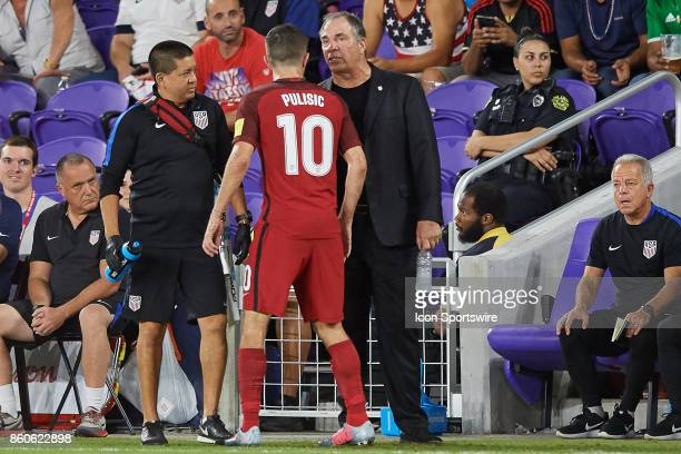 United States head coach Bruce Arena talks to United States midfielder Christian Pulisic after he has to come off the field after an injury during...