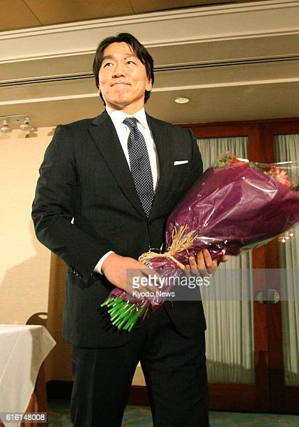 NEW YORK United States Japanese outfielder Hideki Matsui holds a bouquet after a press conference in New York on Dec 27 where he announced his...