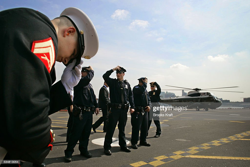 A United States Marine and New York City Police hold their hats as President George W Bush arrives aboard Marine One at the Wall Street Land Zone in...
