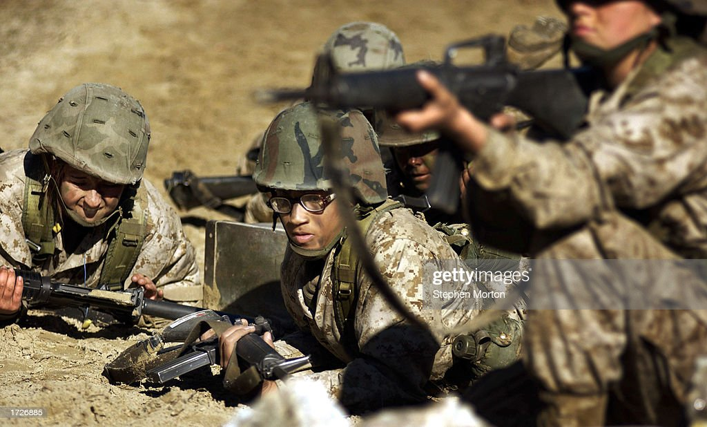 United States Marine Corps female recruits crawl for cover January 15 2003 during a obstacle test course called The Crucible at boot camp on Parris...