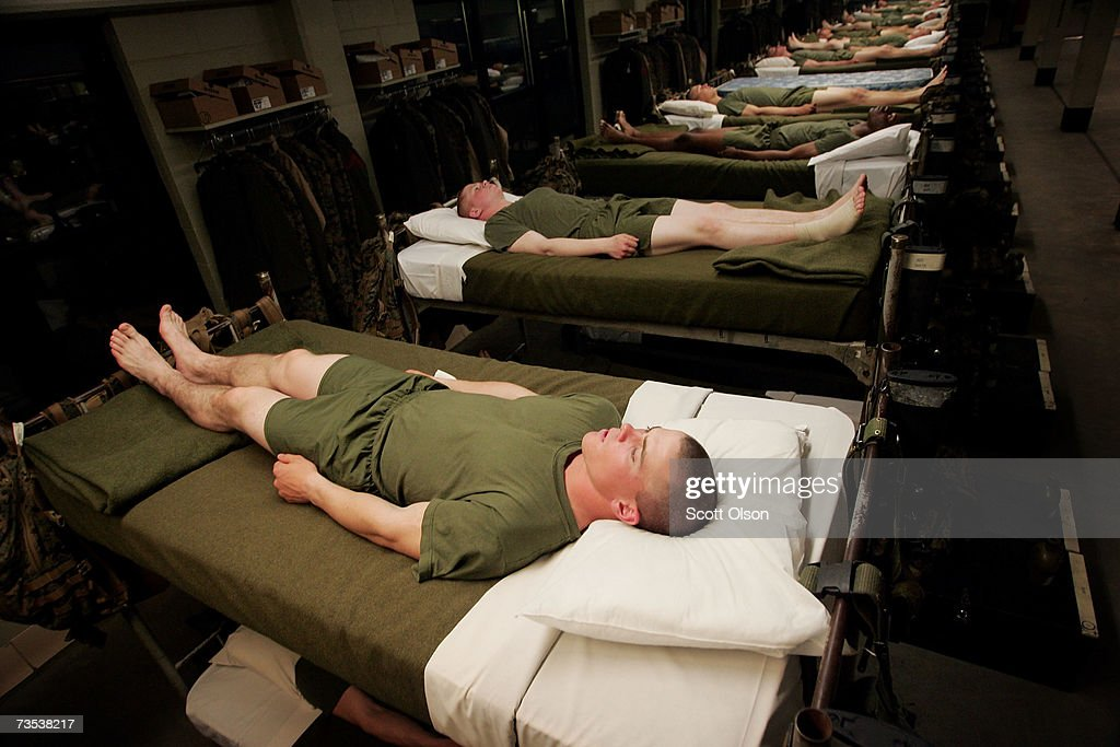 United States Marine Corps recruits lie in bed at the position of attention waiting for lights out to signify the end of the training day during boot...