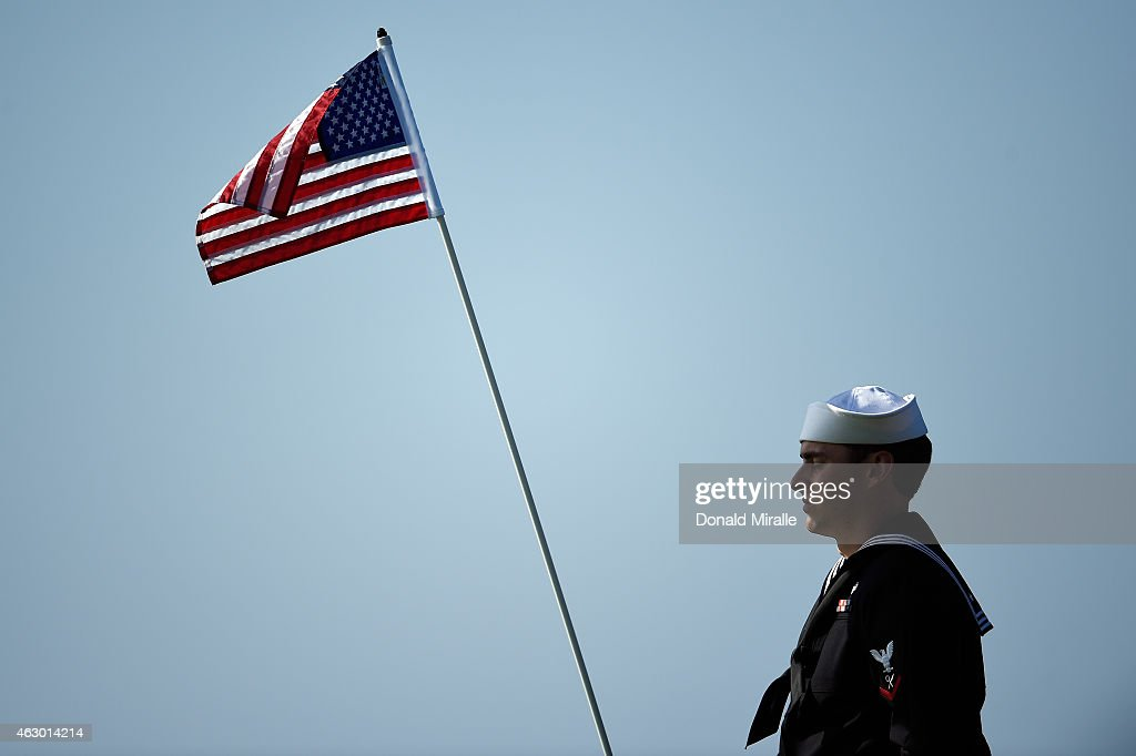 United States Marine holds the pin flag on the 15th green during the final round of the Farmers Insurance Open at Torrey Pines South on February 8...