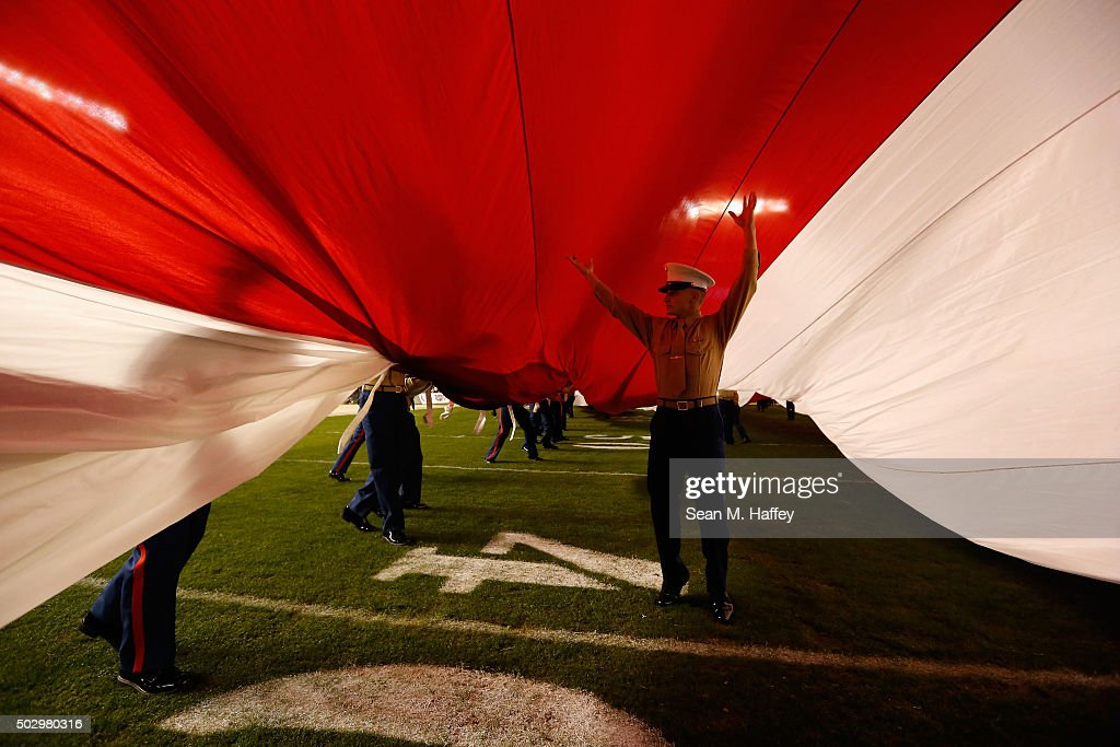 A United States Marine holds up a large flag prior turnover a game between the Wisconsin Badgers and the USC Trojans at the National University Holiday Bowl at Qualcomm Stadium on December 30, 2015 in San Diego, California.