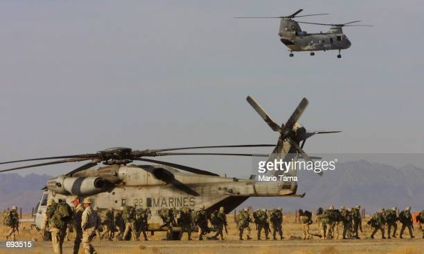United States Marines march in front of Marine helicopters on the American military compound at Kandahar Airport January 21 2002 in Kandahar...