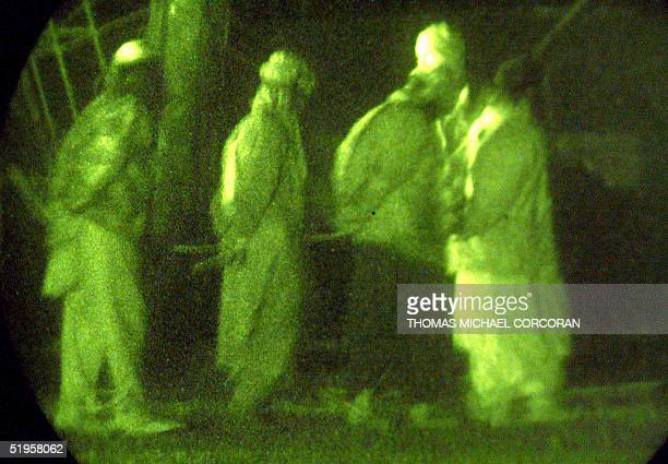 United States Marines shown through a night vision scope escort battle field detainees into a detention center at the Kandahar International Airport...
