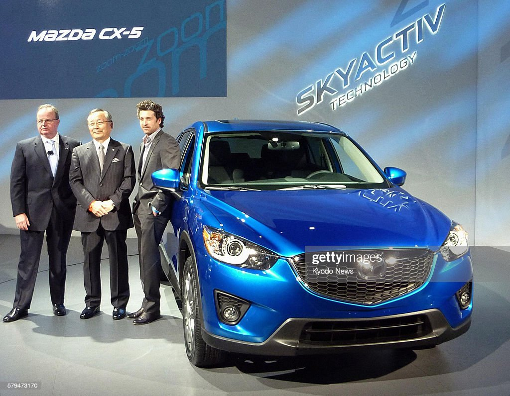 LOS ANGELES United States Mazda Motor Corp President Takashi Yamanouchi stands by the company's CX5 sport utility vehicle unveiled at the Los Angeles...