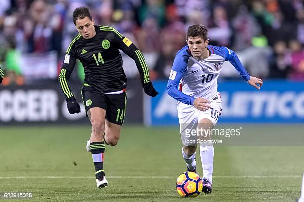 United States Men's National Team player Christian Pulisic dribbles the ball past Mexico Men's National Team player Javier Hernandez in the first...