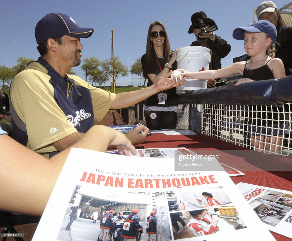 MARYVALE United States Milwaukee Brewers pitcher Takashi Saito hands a signed ball to a fan in Maryvale Arizona on March 27 during a drive to ask for...