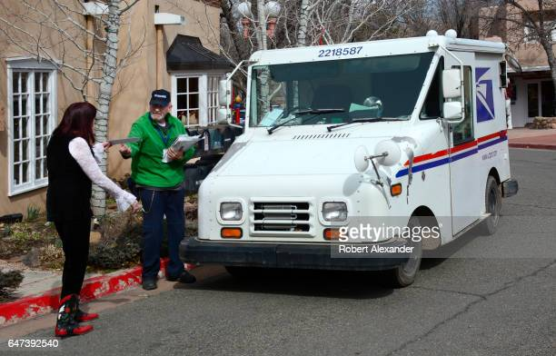 United States Postal Service postman picks up and delivers mail along Canyon Road in Santa Fe New Mexico The USPS mail trucks known as Grumman LLV...