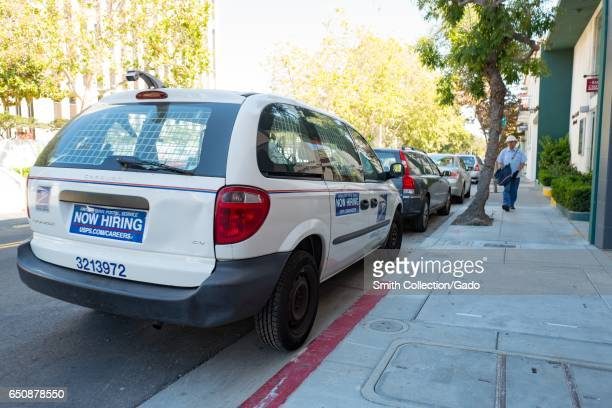 United States Postal Service vehicle with sign reading Now Hiring and postal carrier walking towards the vehicle in the Silicon Valley town of Palo...