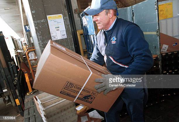 United States Postal Service worker Bill Moody loads packages onto a truck for delivery December 21 2000 at a facility in downtown Boston The US...