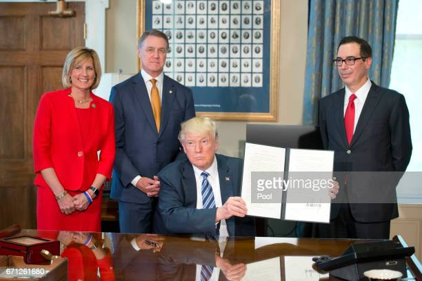 United States President Donald J Trump with Treasury Secretary Steven Mnuchin holds up the order after signing the first of three Executive Orders...
