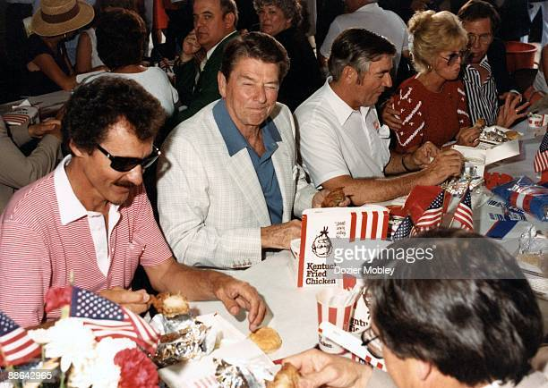 United States President Ronald Reagan enjoys a fried chicken lunch with NASCAR greats Richard Petty and Bobby Allison on July 4 1984 at a banquet...