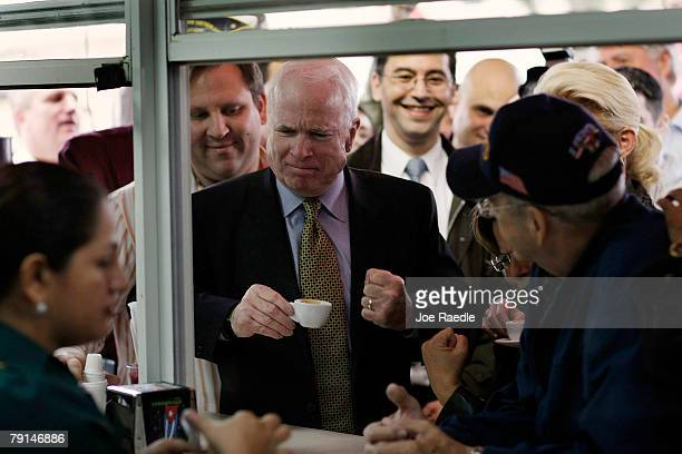 United States Presidential hopeful Sen John McCain pumps his fist after taking a sip of Cuban expresso during a campaign visit to the Versailles...