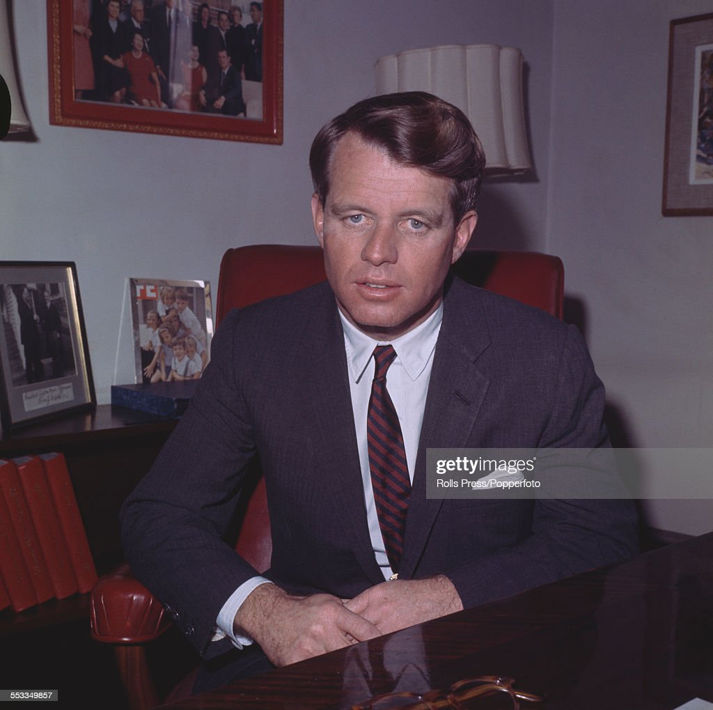 United States Senator for New York, Robert F. Kennedy (1925-1968) pictured in his office surrounded by photographs of the Kennedy family circa 1965.